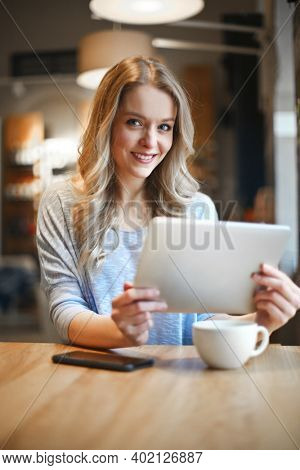 young woman in a cafe with a tablet