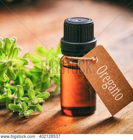Oregano Essential Oil And Fresh Leaves On Wooden Background