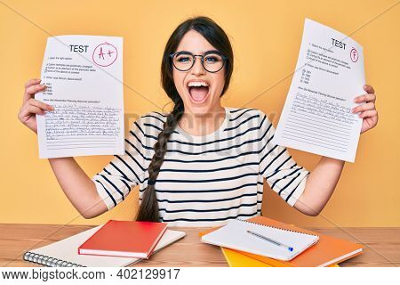 Brunette teenager girl showing failed and passed exam smiling and laughing hard out loud because funny crazy joke.