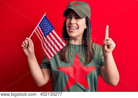 Beautiful woman wearing t-shirt with red star communist symbol holding united states flag smiling with an idea or question pointing finger with happy face, number one