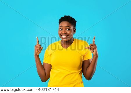 Look Upward. Cheerful African Plus-size Lady Pointing Fingers Up Standing Posing On Blue Studio Back