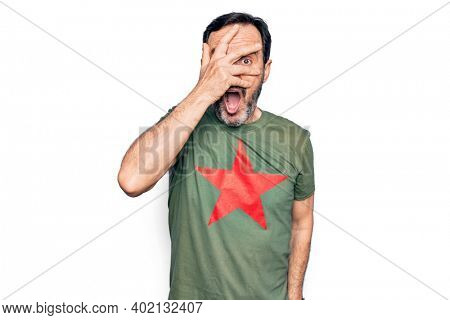 Middle age handsome man wearing t-shirt with revolutionary red star over white background peeking in shock covering face and eyes with hand, looking through fingers afraid
