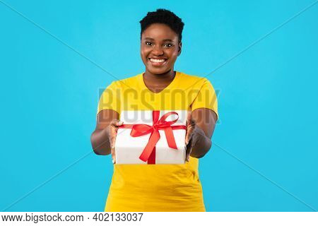 Cheerful Plus Size African Woman Offering Wrapped Gift Box To Camera Posing Standing Over Blue Studi