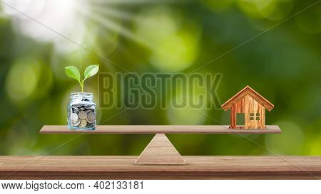 House And Tree Planted In Bottles Saving Money Placed On Wood Scales In Parks, Savings Ideas For Buy