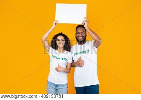 Two Multiethnic Volunteers Holding Blank White Paper Board Above Head Gesturing Thumbs Up, Approving