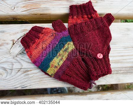 Handcrafted Handmade And Knitted Knitwear Traditional Colorful Children's Gloves Laid On A Wooden Ta