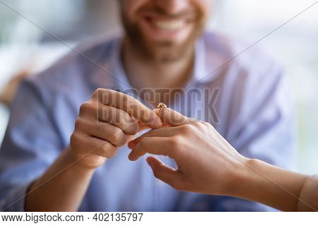 Happy Guy Holding His Fiancees Hand, Putting On Engagement Ring On Her Finger, Closeup View. Unrecog