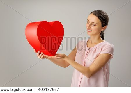 The Girl Holds A Large Red Heart In Her Hands And Smiles Cheerfully