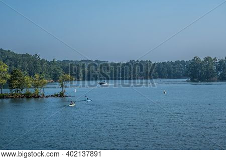 A Couple Of Kayakers And A Motorboat Causing A Wake Going By With The Woodlands In The Background A