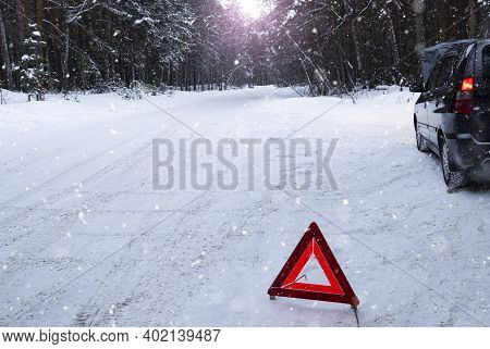 In A Snowy Forest, A Car Broke Down On The Road. A Red Warning Triangle Is Installed On The Snow