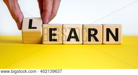 Learn Or Earn Symbol. Businessman Hand Turns A Cube And Changes The Word 'earn' To 'learn'. Beautifu