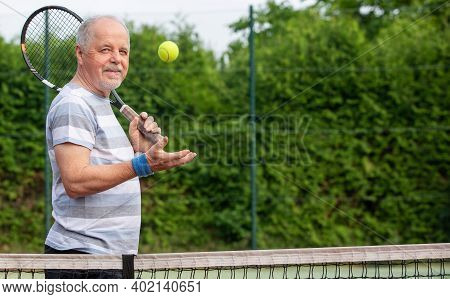 Portrait Of An Active Senior Man At The Tennis Court With Racket And Tennis Ball, Sport Concept