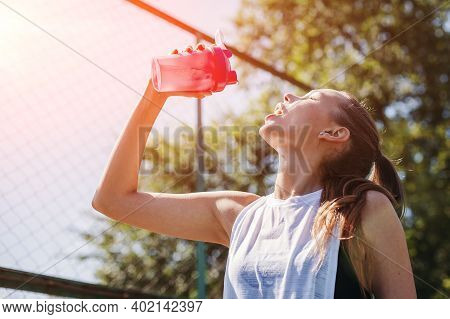 Sporty Young Blonde Woman With A Sporty Bottle With Cool Water Pours Water On Herself On The Sports
