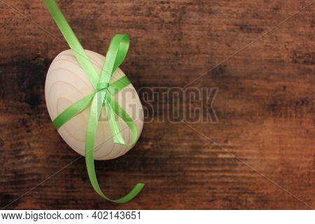 Blank Wooden Easter Egg Tied With Green Ribbon For Painting Or Decoupage On Wood Background. Top Vie