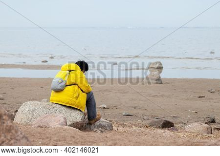 Burdened By Unseen Worries. Sad Lonely Man In Yellow Raincoat Sits On Stone At Seashore Looking Forw