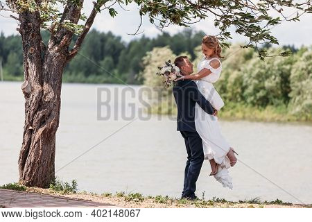 Panoramic View At Young Couple Bride In White And Groom In Blue Standing Among Lake Under A Tree, Po