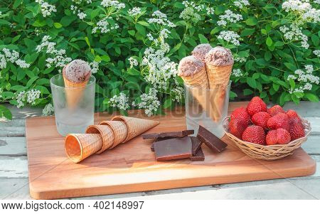 Waffle Cones With Chocolate Ice Cream In Glasses As Stand, Pieces Of Dark Chocolate, Basket Of Fresh