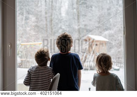 Three Kids, Siblings, Looking Out The Window At A Beautiful Snowy Nature.