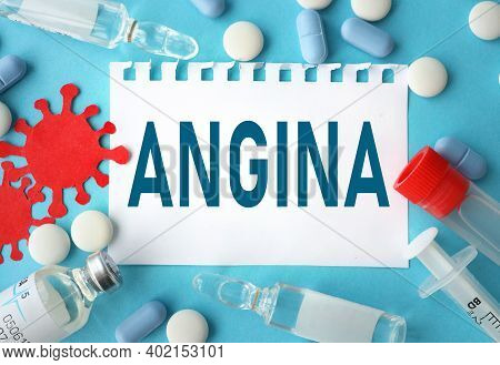 Angina, Text On White Paper On A Blue Background. Near Ampoules, Tablets, Capsules, Transparent Jars