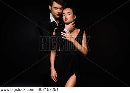 Passionate Man Choking Sexy And Submissive Woman In Dress Isolated On Black