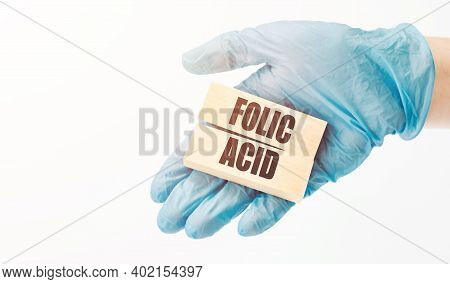 Folic Acid Written On A Card In A Doctor's Hand.