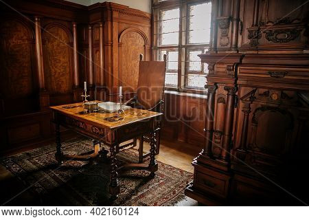 Castle Interior. Cabinet With Writing Desk With A Book And Candlesticks, Room With Baroque And Renai