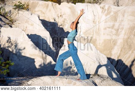 A Young Slim Woman Doing Yoga Exercises In The White Limestone Mountains. The Girl Travels In Nature