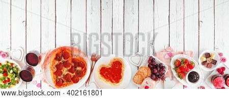 Homemade Valentines Day Dinner. Top View Bottom Border On A White Wood Background. Heart Shaped Pizz
