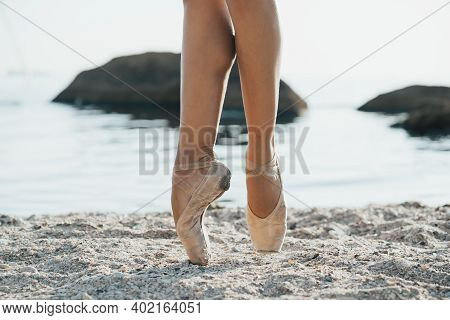 Close Up Of Ballet Dancers Feet. She Practices Exercises On Sandy Beach. Womans Legs In Pointe Shoes