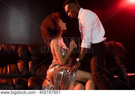 African American Man In Suit Seducing Woman In Dress On Black