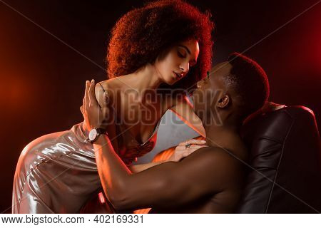 Sexy African American Woman In Dress Seducing Shirtless Man On Black Background