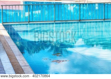 Green Palm Trees Reflexion On A Pool With Azure Water