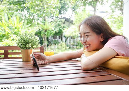 Asian Woman, 40 Years Old Happy Holding A Smartphone Playing Social Media Online On The Balcony Of H