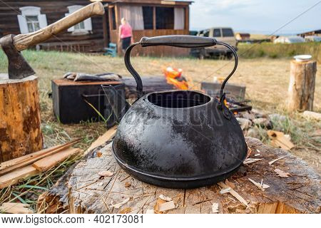 A Black Kettle Stands On A Stump Near Fire In The Courtyard Of An Old Country House. Making Fresh Te