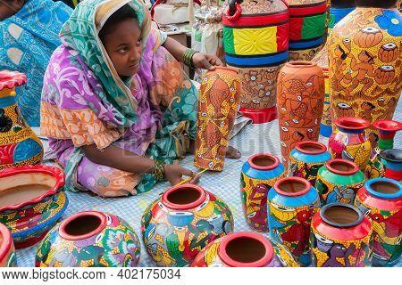Kolkata, West Bengal, India - 31st December 2018 : Female Indian Artist Painting Colorful Terracotta