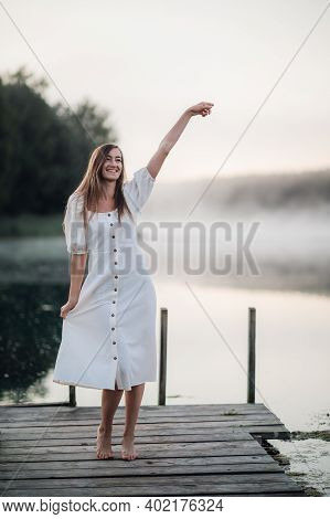 Happy Woman In A White Dress Enjoys Morning On A Lake. Fog Floats Over The Water.