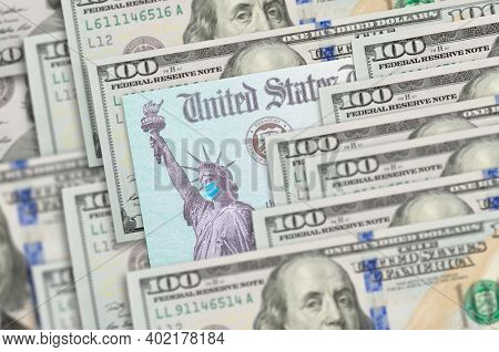 United States IRS Stimulus Check with Statue of Liberty Wearing Medical Face Mask Resting on Hundred Dollar Bills.