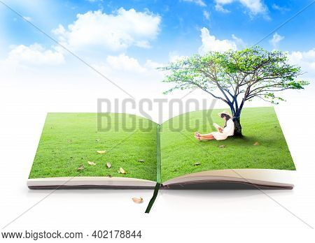 World Environment Day Concept: Asian Children Reading Under Big Tree On Book Of Nature