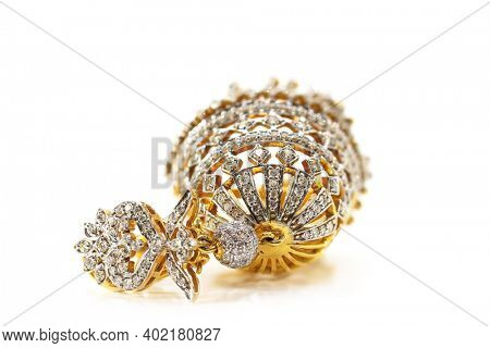 Golden earring with real diamonds on white background