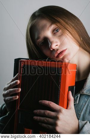 A Beautiful Young Model Holds An Old Cassette Recorder In Her Hands