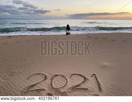 Traveler walking on tropical beach in vacation. lifestyle woman relax and freedom on sea beach, 2021 inscription on the sand of the beach