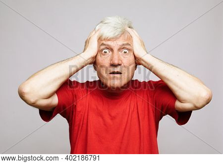 Portrait of anxious senior man in red t-shirtholding his head. I'm afraid that I will be exposed and someone will know my terrible secret emotion