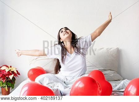 Young Happy Brunette Woman Sitting Awake In The Bed With Red Heart Shaped Balloons