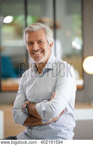 Portrait of senior businessman with arms crossed looking at camera