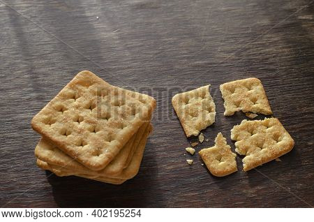 Groceries, Snacks, Food. Stack Of Salted Crunchy Crackers On A Wooden Table.  One Cracker Divided In
