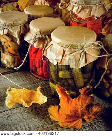 Autumn Concept. Preserved Food In Glass Jars On A Wooden Board. Marinated Food