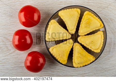 Three Red Tomatoes, Few Small Savory Pies In Glass Brown Saucer On Wooden Table. Top View