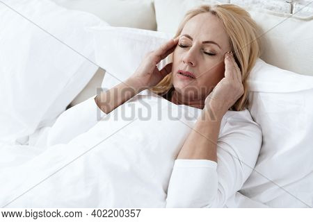 A Woman Has A Headache Lying In Bed.