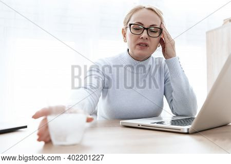 Business Woman In A Shirt Sitting In The Office And Holding On To A Sore Shoulder. Girl With Glasses