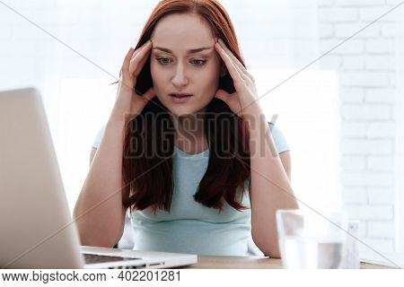 Pregnant Woman Sits At A Desk And Holding On To Her Sore Head. Girl Put Her Hand On A Pregnant Belly
